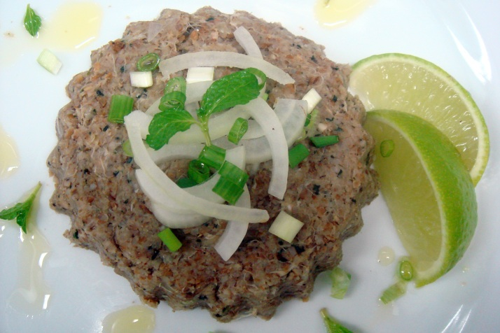 Kibe cru, mesma receita da massa do kibe, servido com folhas de hortelã, cebolinha, cebolas em tiras e limão