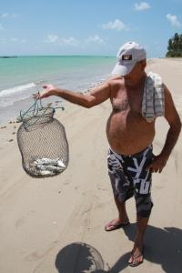 Um pescador mostra seus peixes fresquinhos